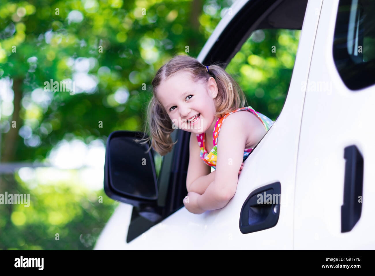 Little Girl With Funny Pigtails Watching Out Of Car Window