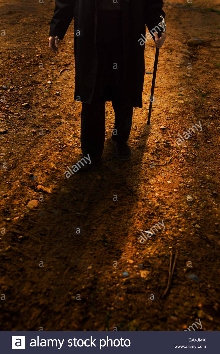 Unknown Man Wearing A Long Black Coat And A Walking Stick Stock