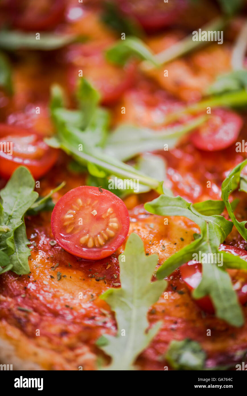 close view on fresh pizza ingredients, tomatoes and rucola ...