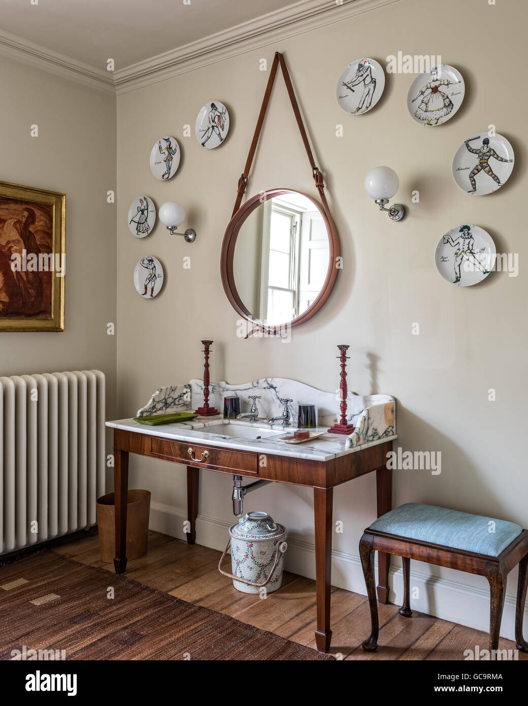 fornasetti harlequin plates on wall around a modern mirror from conran the marble topped vanity unit is made by nick coryndon