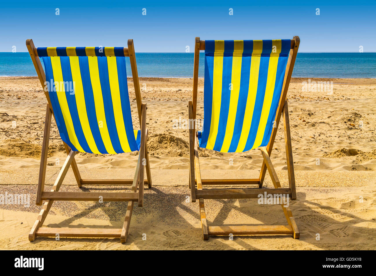 Two Blue And Yellow Deck Chairs Facing The Sea Across Golden Sand On A  Bright Sunny Day, Bournemouth, UK
