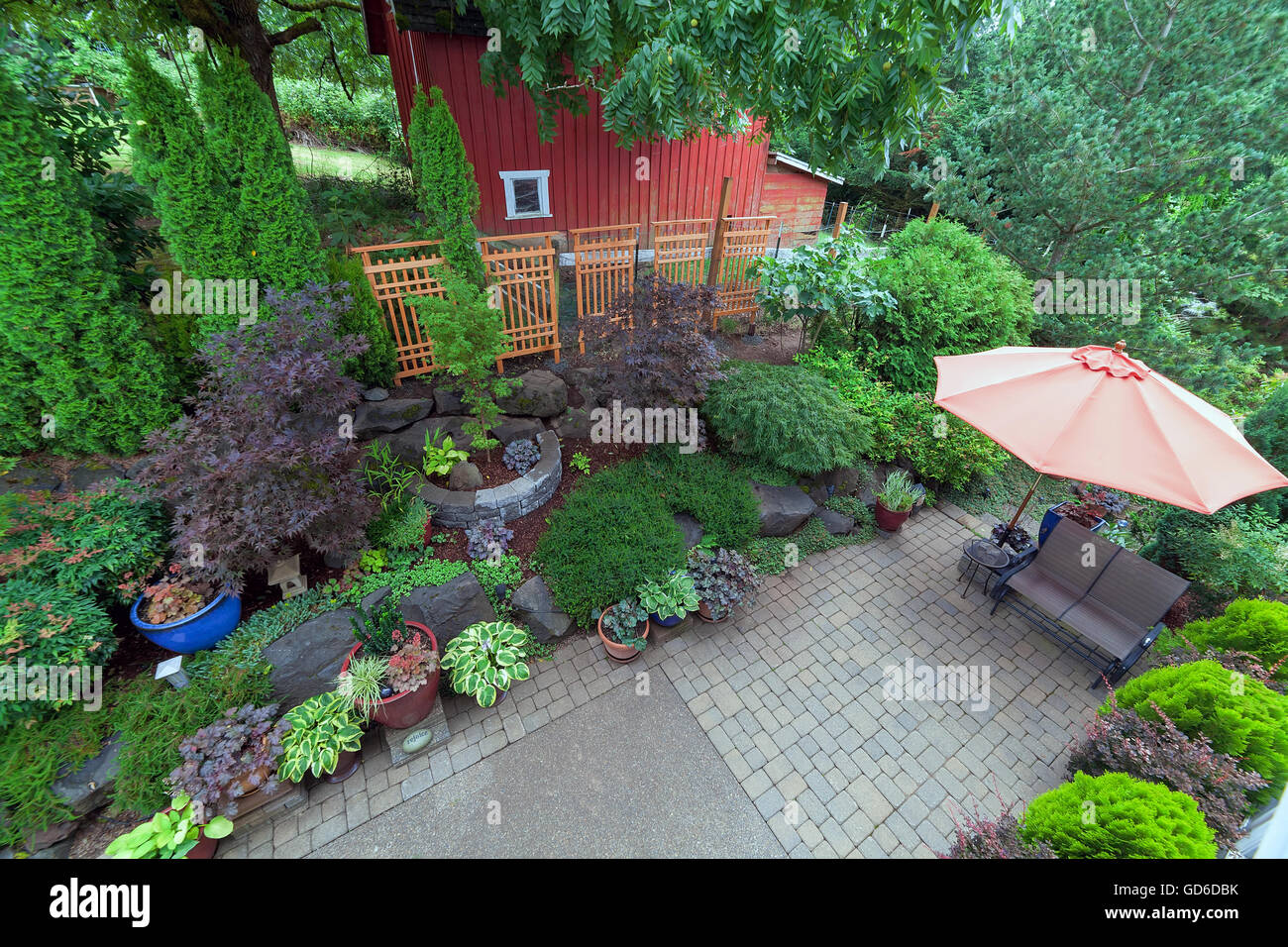 Backyard Garden Landscaping With Paver Bricks Patio Hardscape Trees Potted  Plants Shrubs Pond Rocks Furniture And