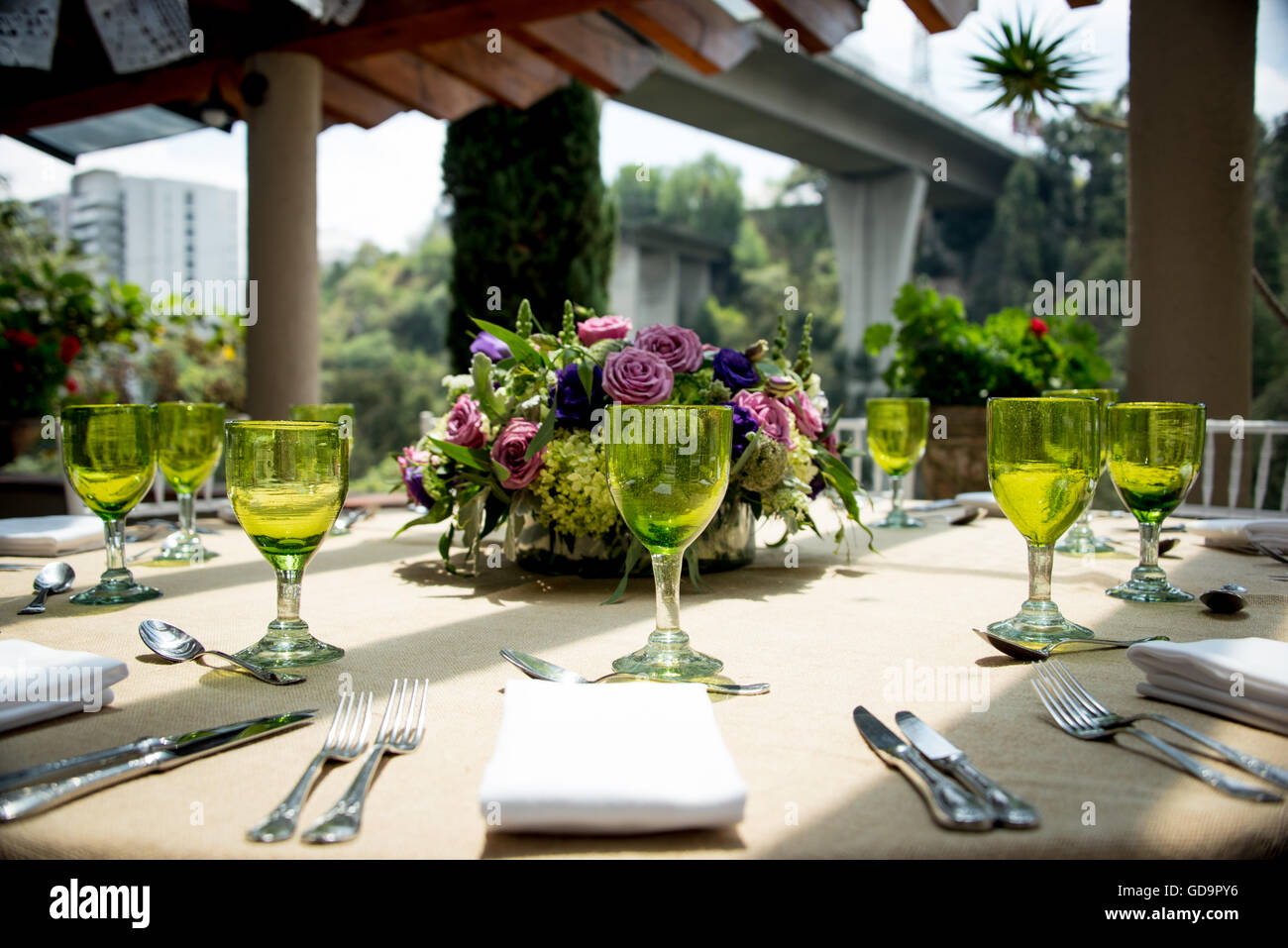 Stylish table setting for an open-air wedding with green wineglasses silverware and linen on a table on a sunny urban patio & Stylish table setting for an open-air wedding with green ...