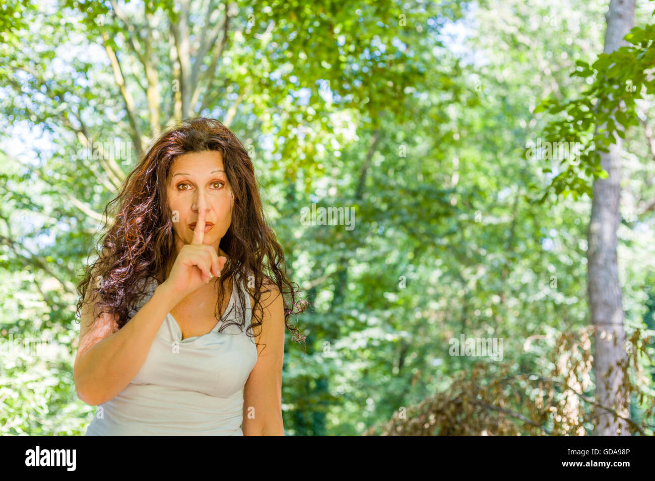 Curvy classy mature woman put index finger to lips for silence in ...