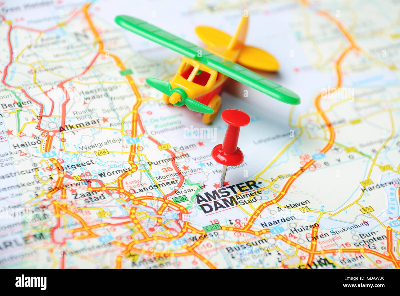 Close up of Amsterdam Netherlands map with red pin and airplane