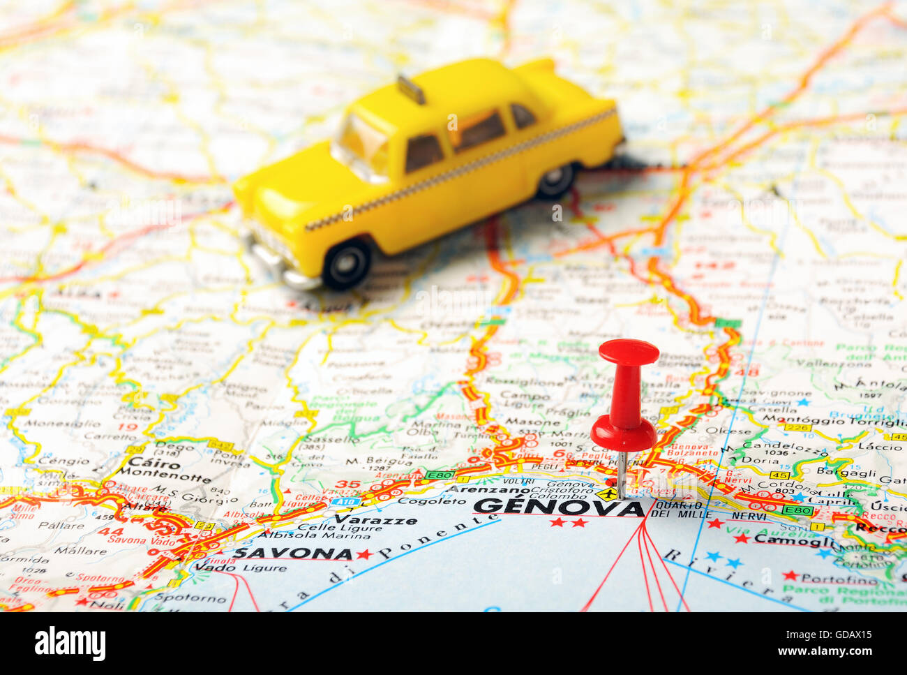 Red push pin pointing at GenovaGenua Italy map and a taxi Stock