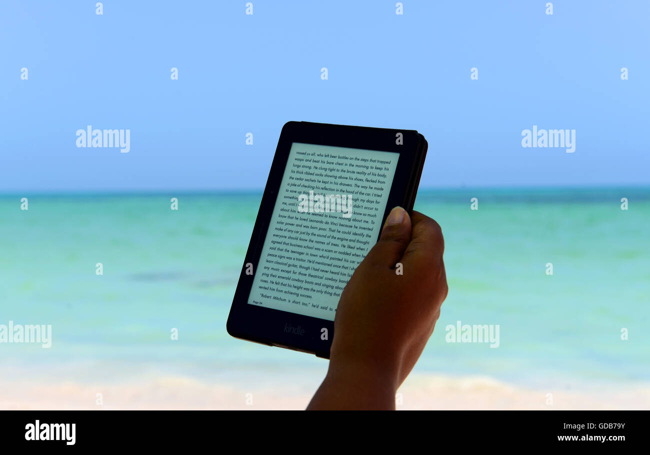 Reading An Ebook With A Kindle On A Beautiful Caribbean Sea In Cuba