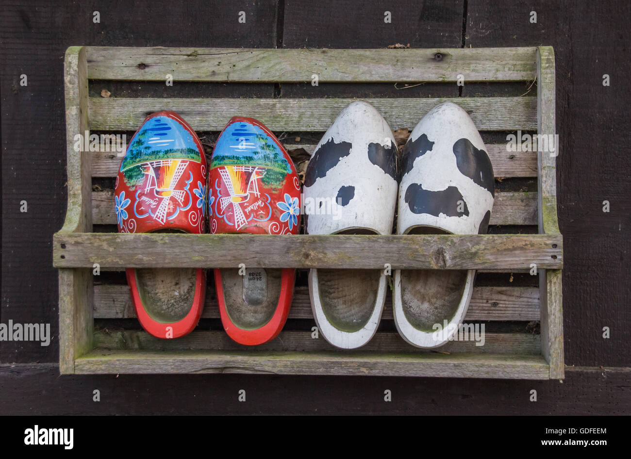 two pairs of wooden shoes in a rack stock photo royalty free