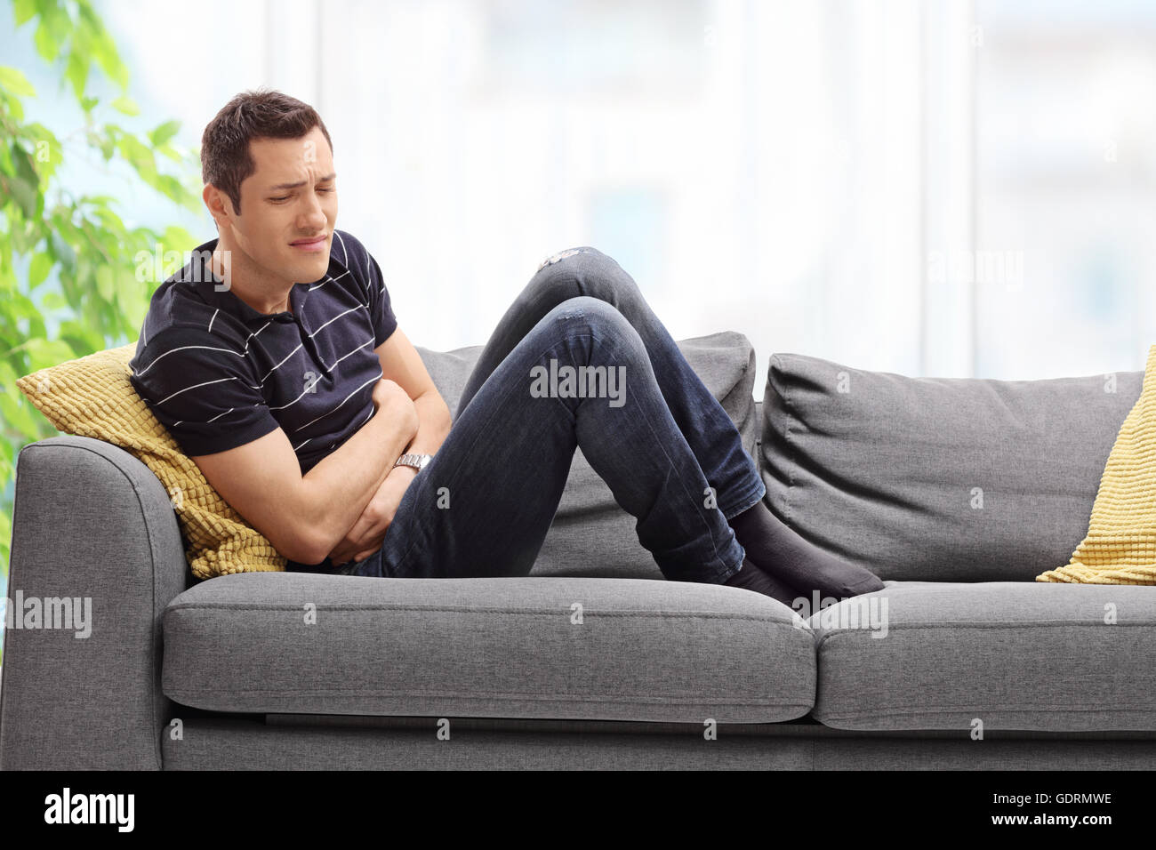 Young guy experiencing stomach pain seated on a couch at home ...