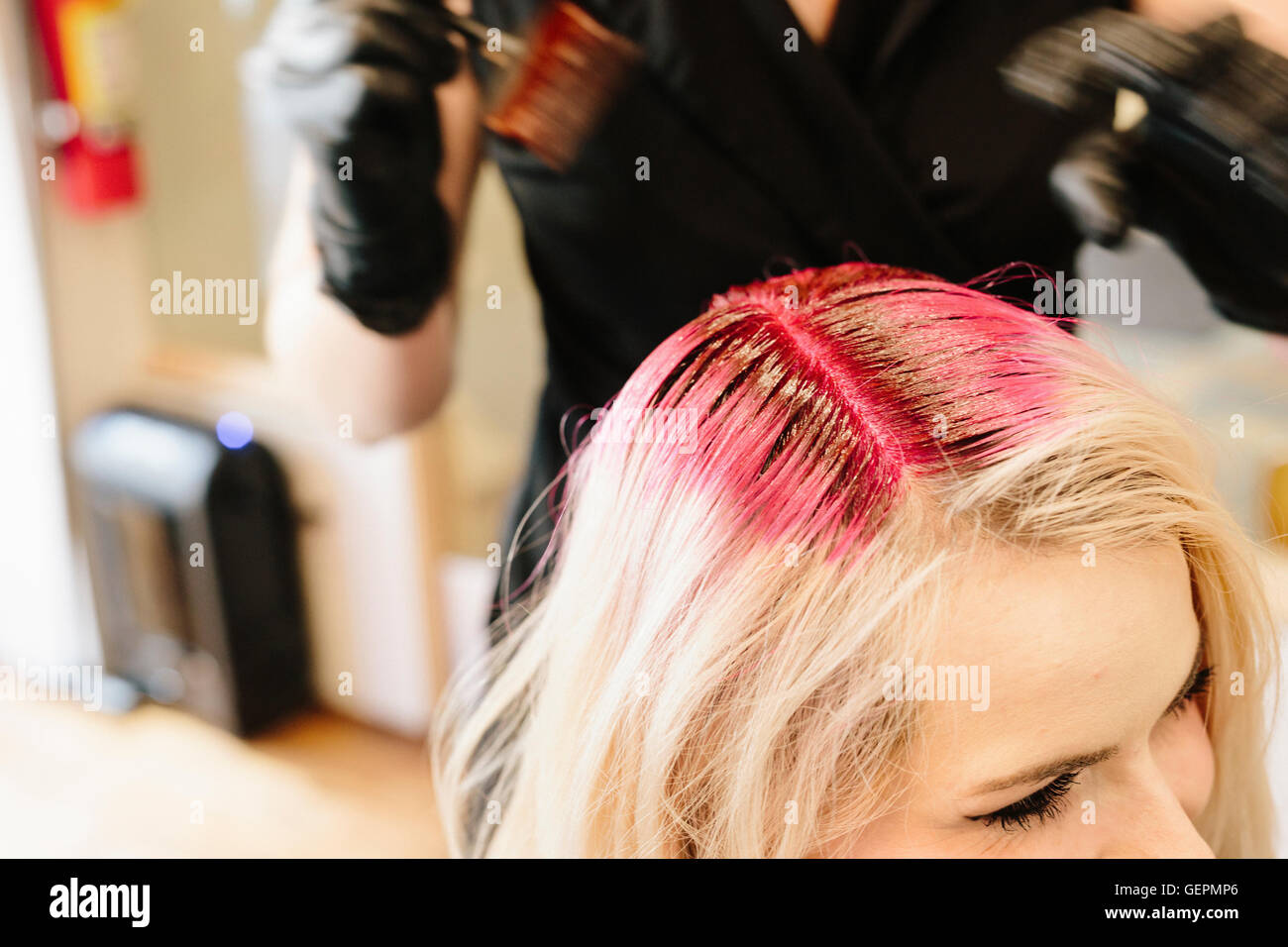 A hair colourist in gloves applying red hair dye to a client\'s ...
