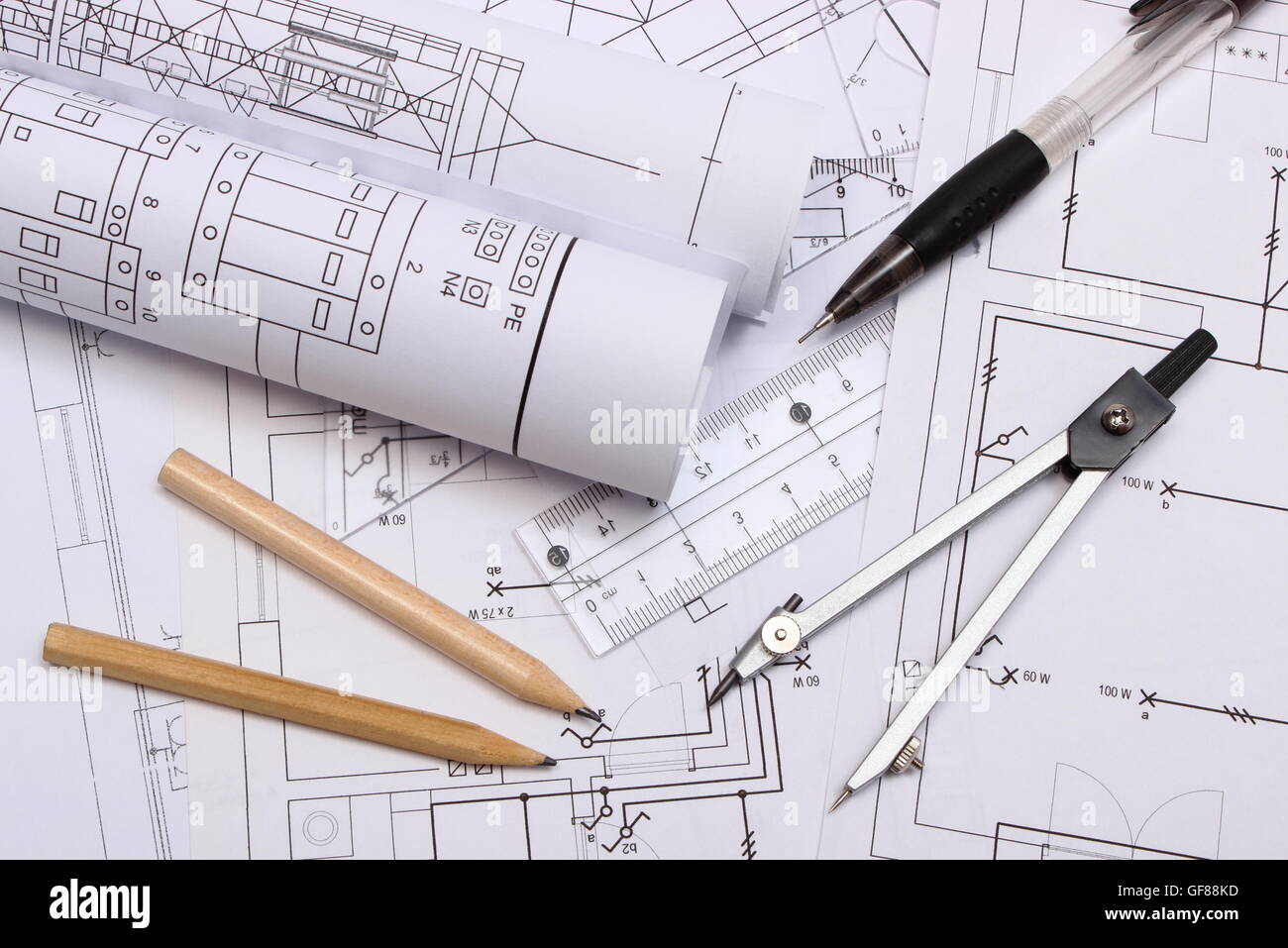 rolls of electrical diagrams and accessories for drawing lying on construction drawing of house drawings