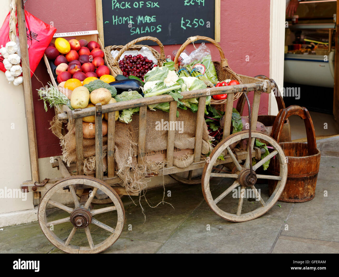 Fruit and vegetables displayed in an old wooden hand cart outside a small general stores