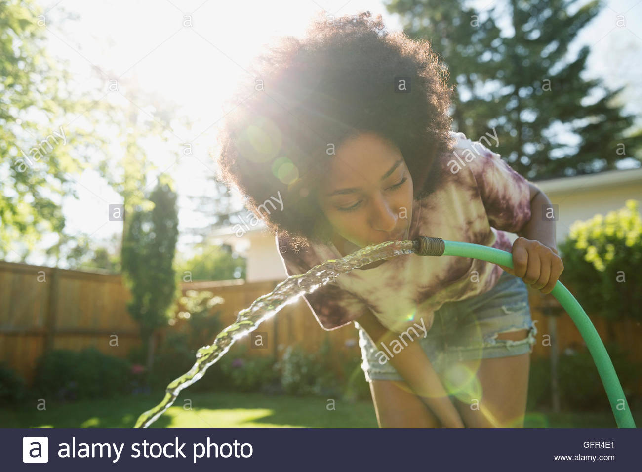 woman drinking water from hose in sunny backyard stock photo