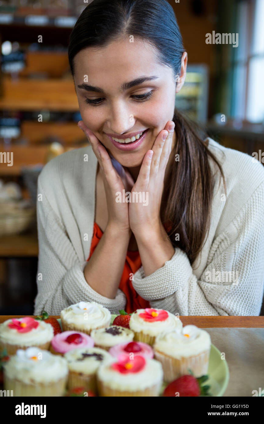 Happy Woman Looking At A Plate Of Cupcakes