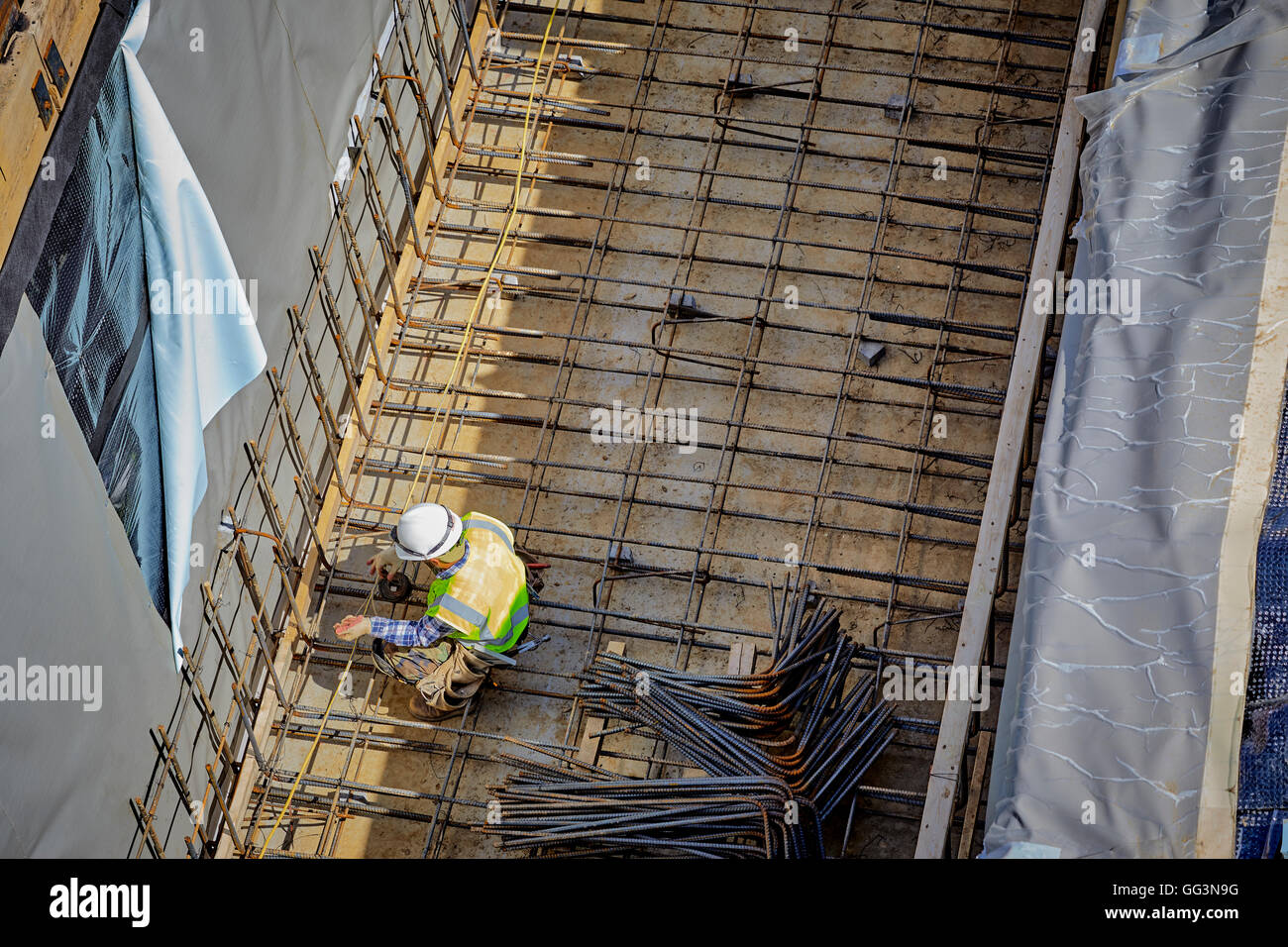 Construction Worker Laying Rebar And Wire For Concrete Basement Foundation