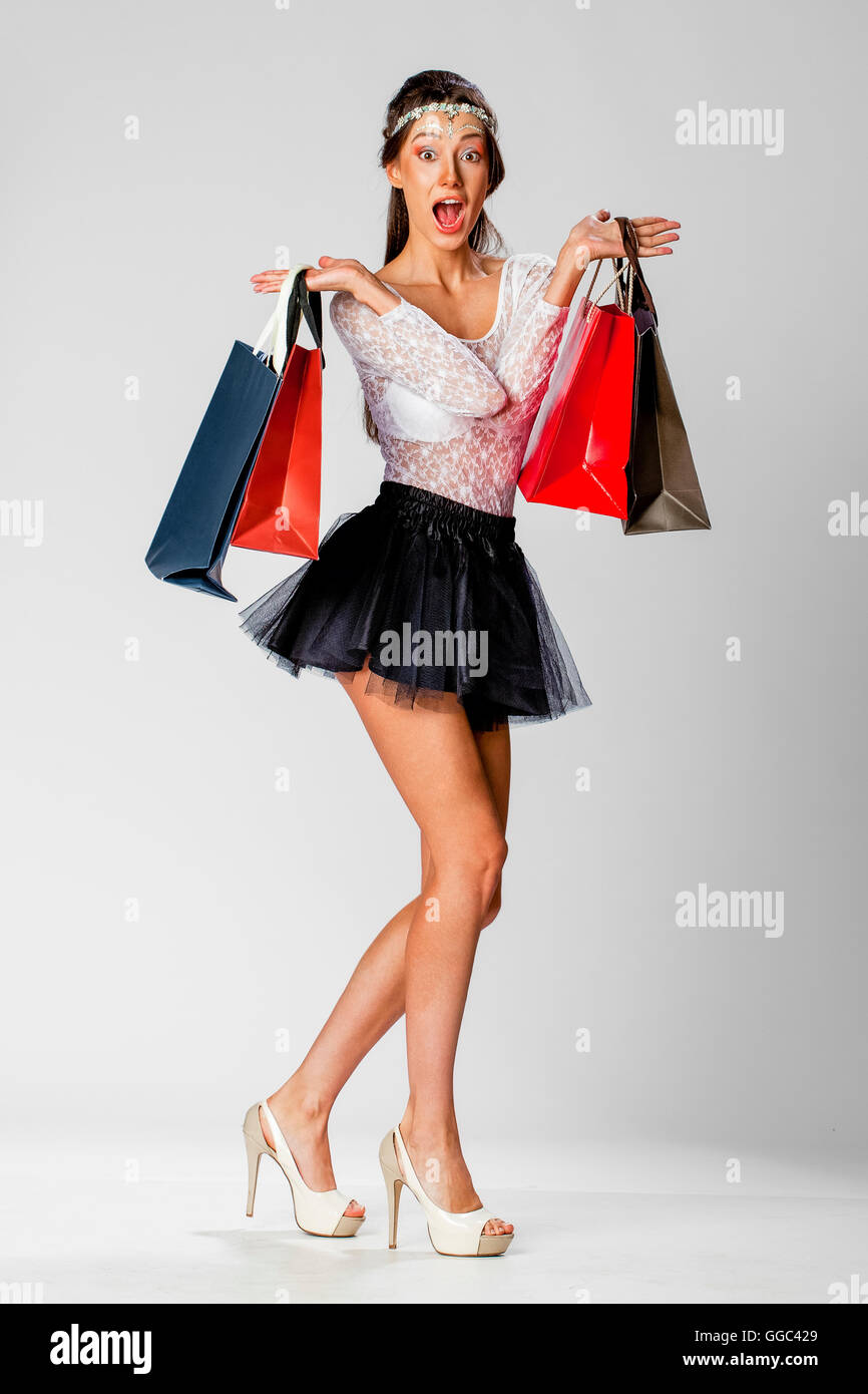 Woman posing with shopping bags isolated on white background full - Full Length Portrait Of A Beautiful Young Brunette Woman Posing With Shopping Bags Isolated On White Background