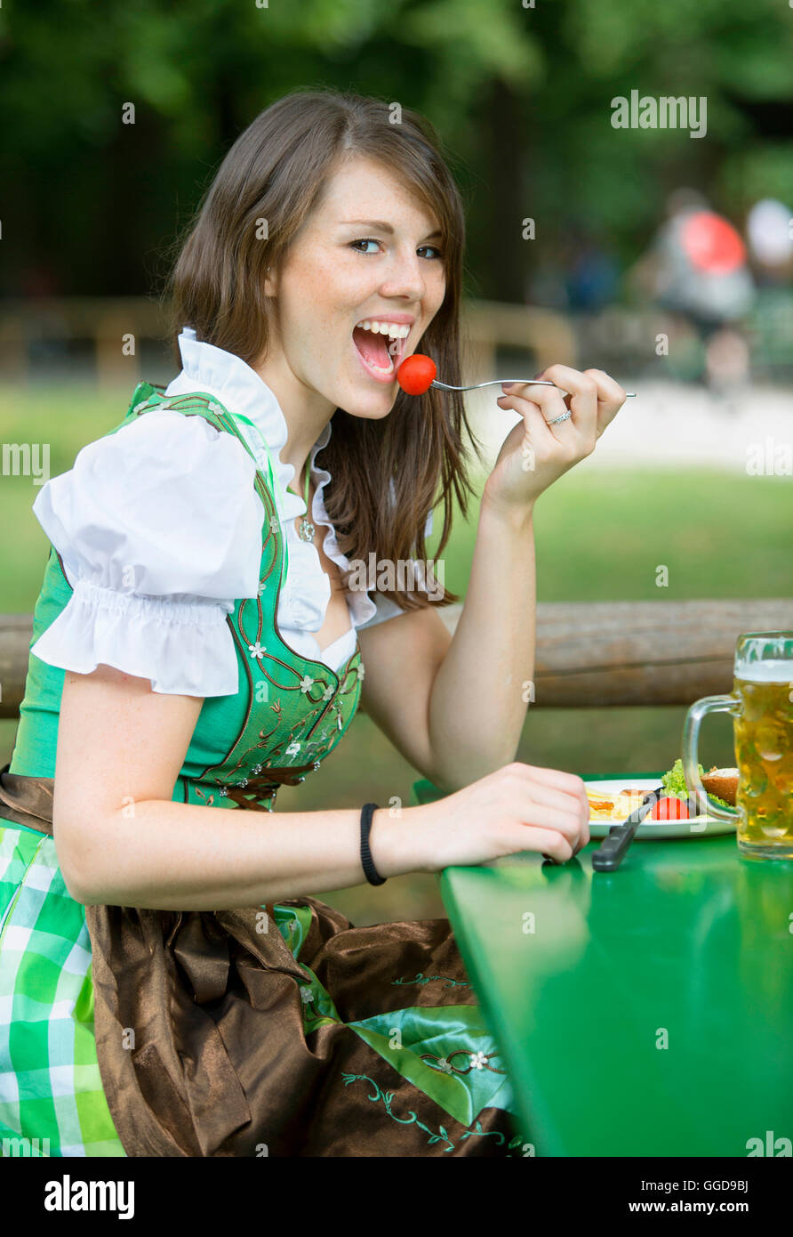 Young Bavarian Woman In Dirndl Sitting Outside With Beer