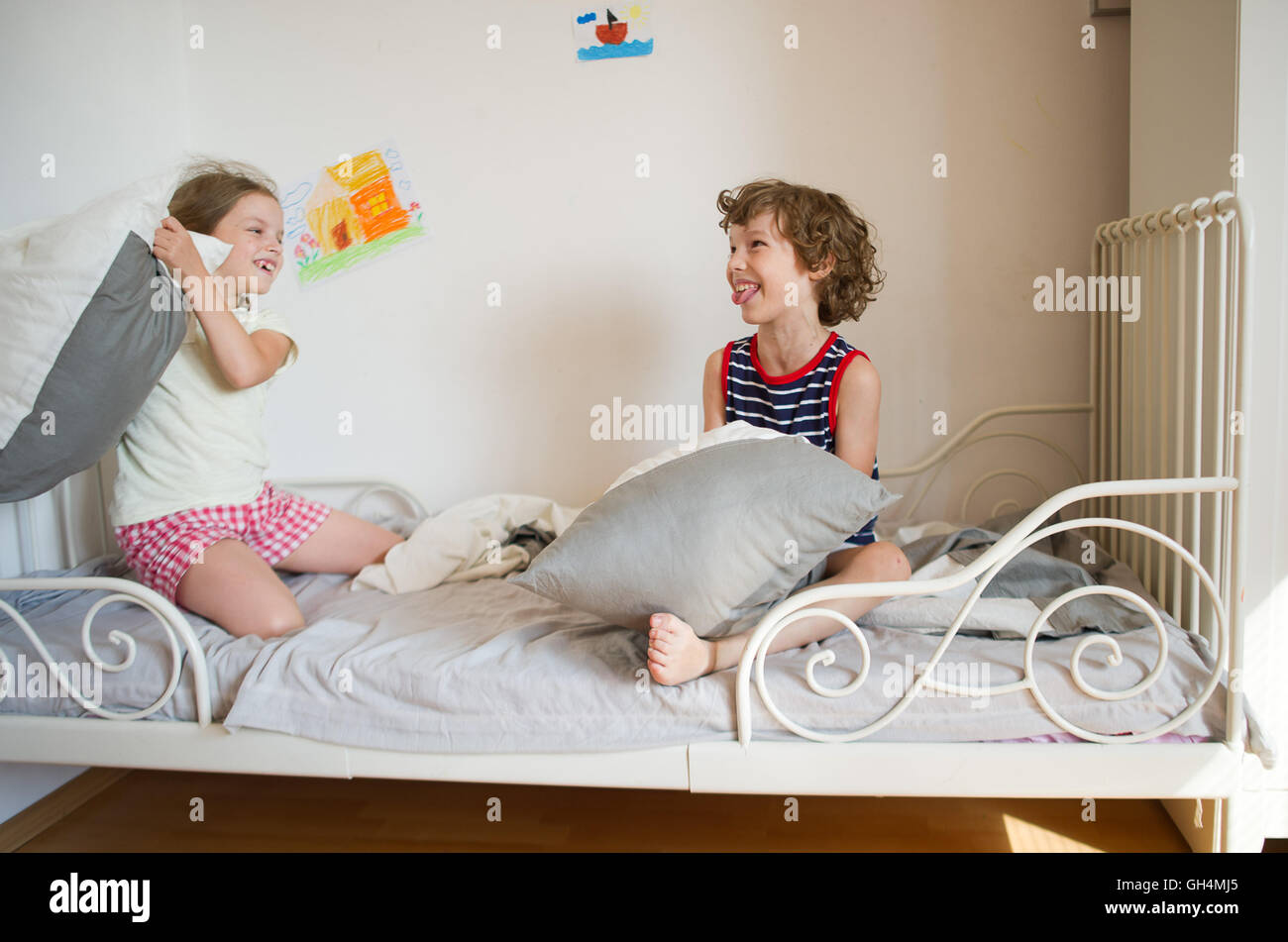 Brother and sister sit on the bed in the bedroom They fight