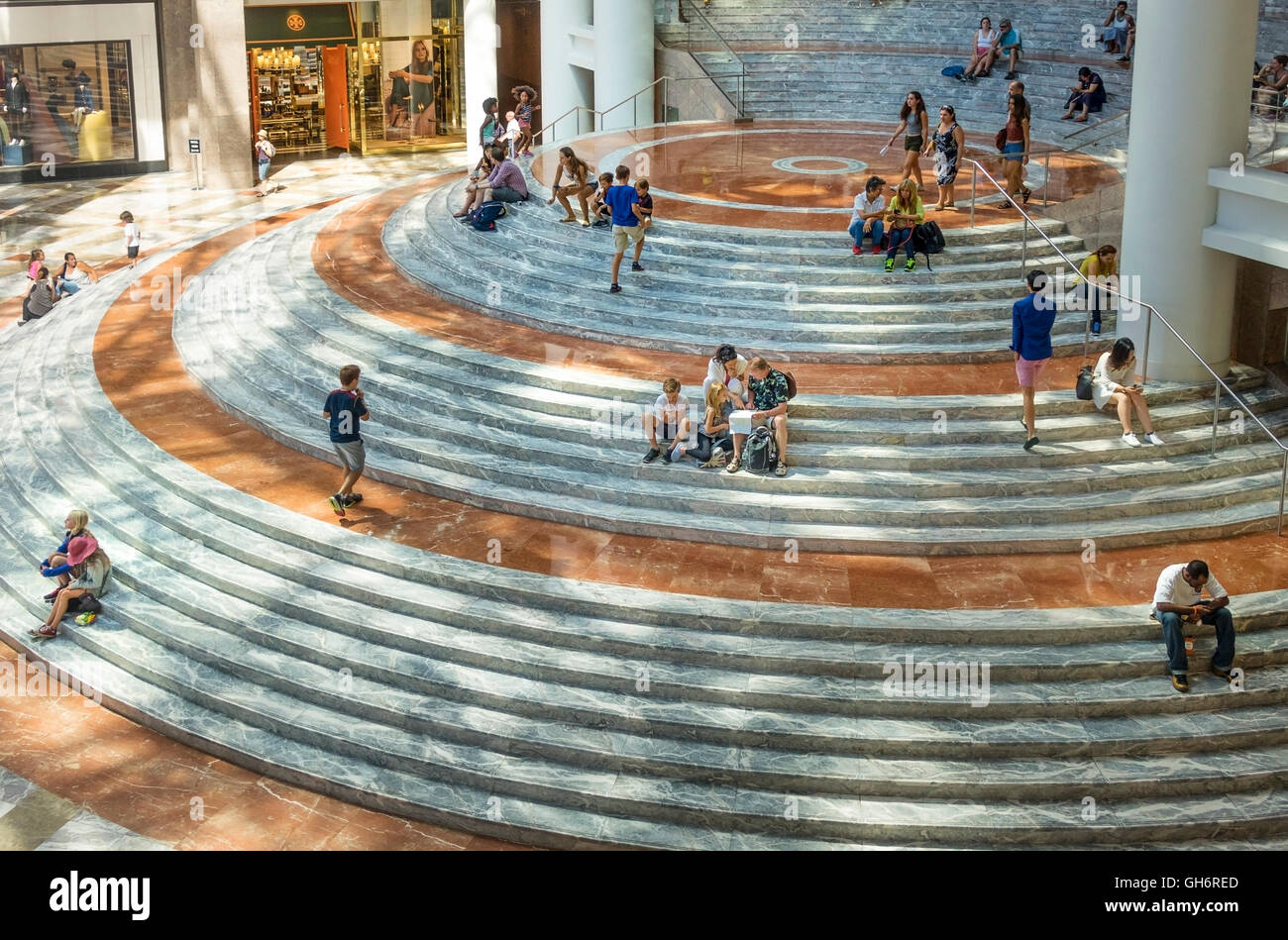 visitors sitting on the curved marble steps in the winter garden