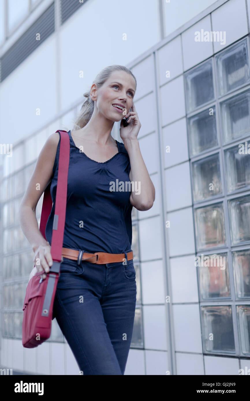 mature woman, walking outdoor, using smartphone stock photo
