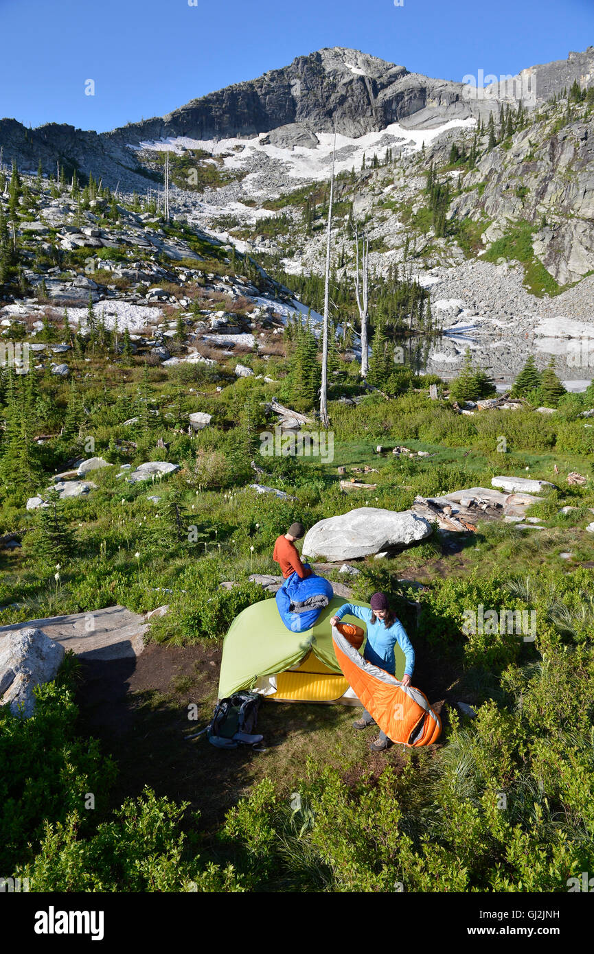 Backpacking couple packs up tent and sleeping bags at Fault Lake in the Selkirk Mountains Idaho & Backpacking couple packs up tent and sleeping bags at Fault Lake ...