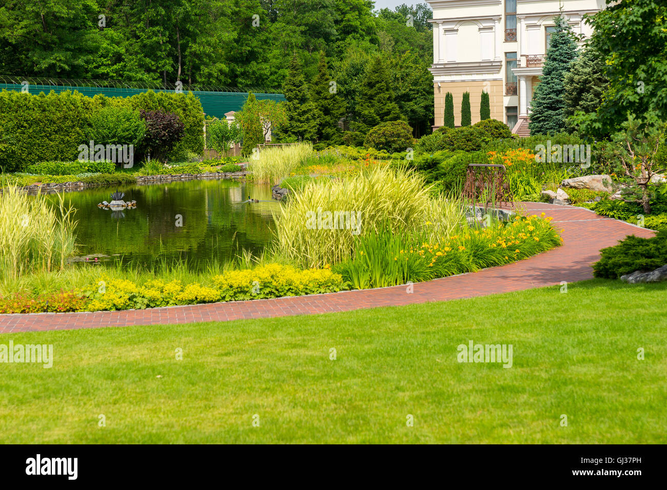 Landscape Design With Beautiful Man Made Lake And Different Trees, Bushes,  Flowers