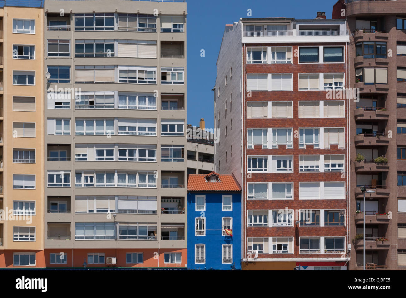 Colourful Small Short House In Between Large Apartment Buildings - Small apartment buildings