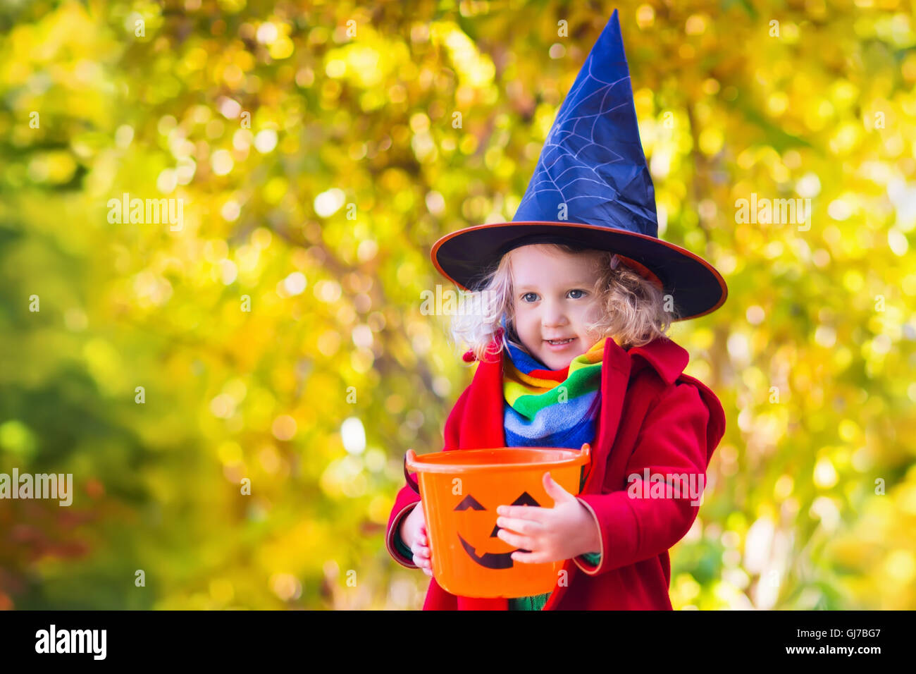Little girl in witch costume playing in autumn park. Child having ...