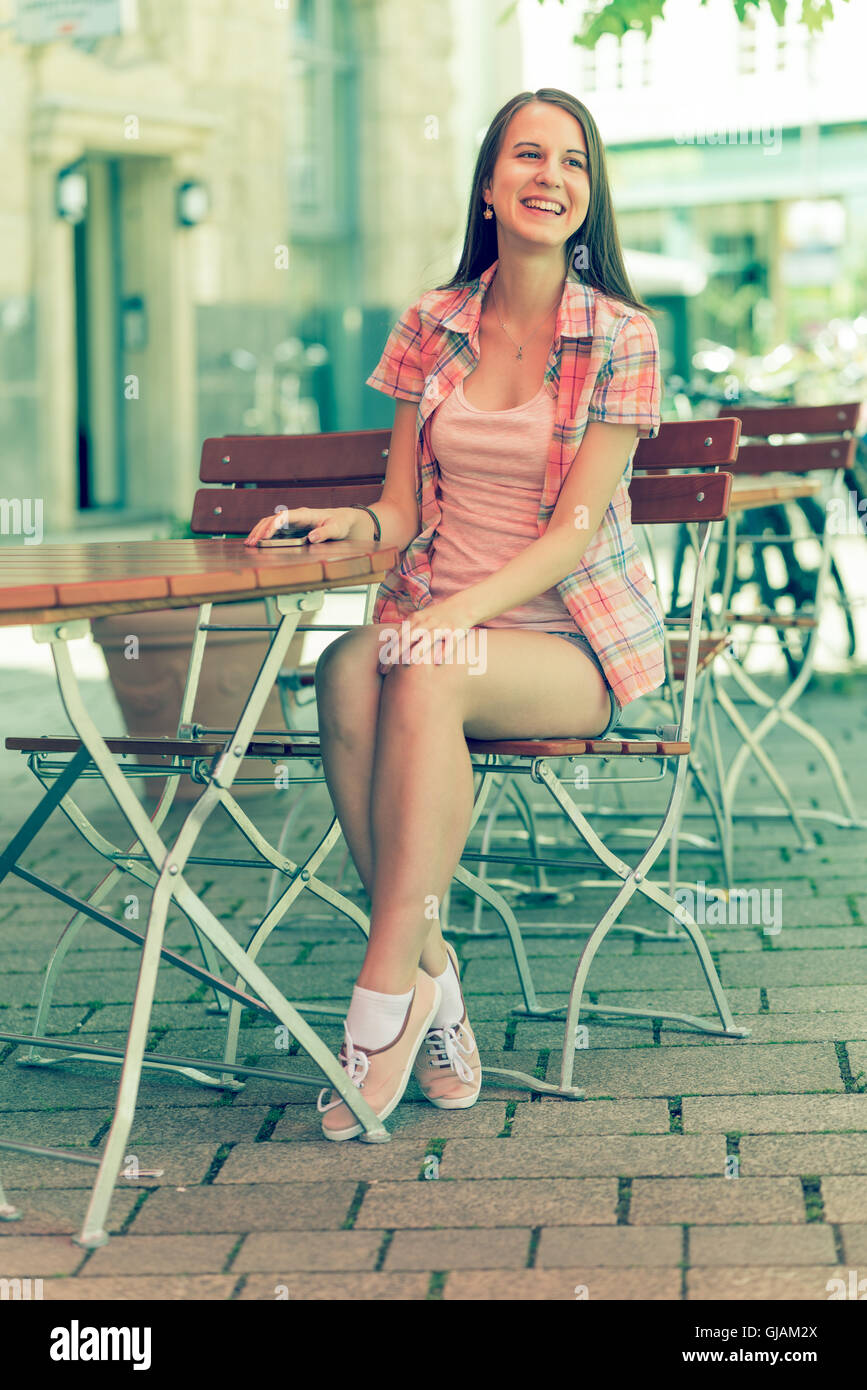Young Woman Wearing Shorts Seat At Table In Street Cafe