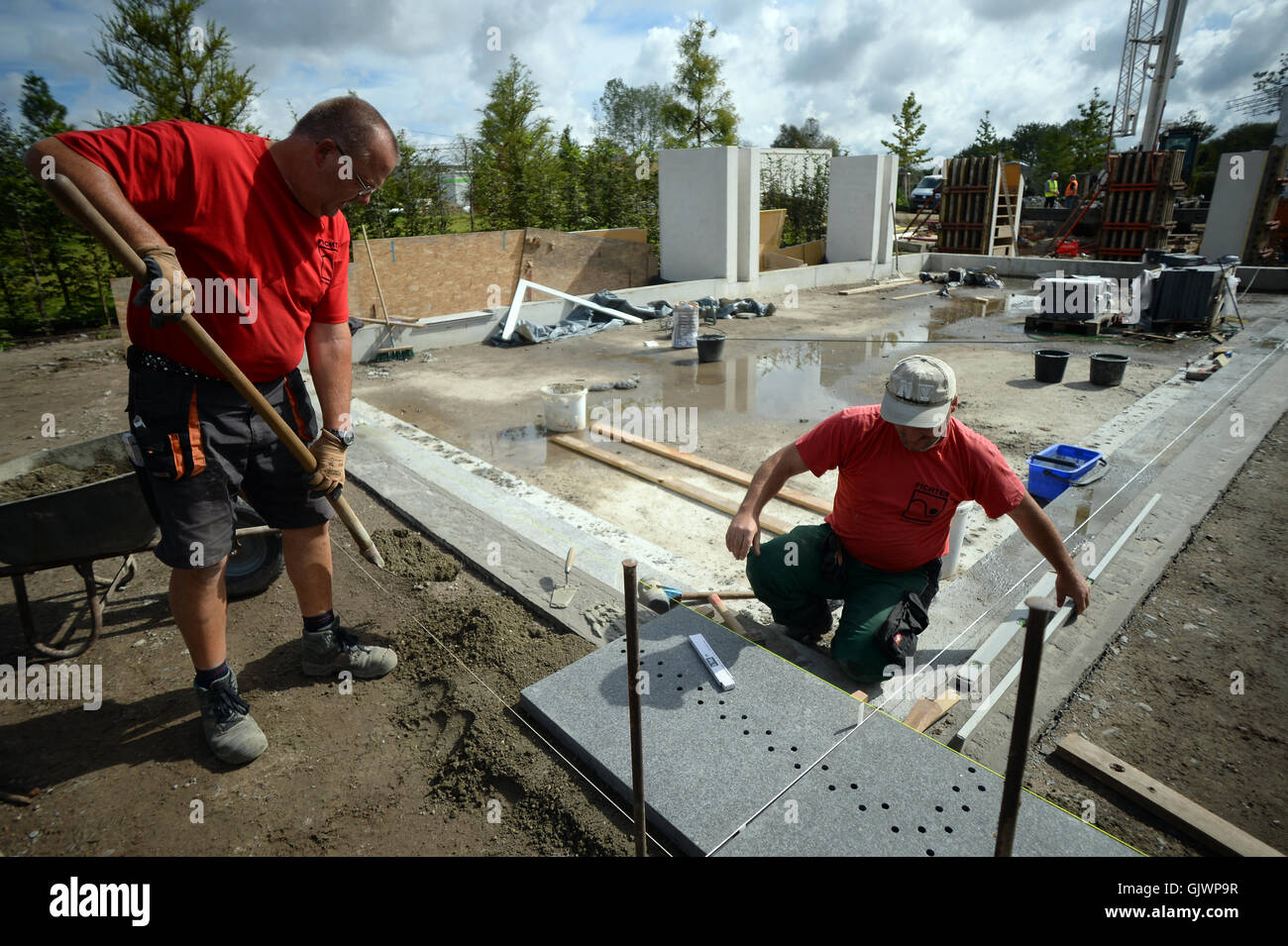 berlin, germany. 17th aug, 2016. workers lay granite tiles at the