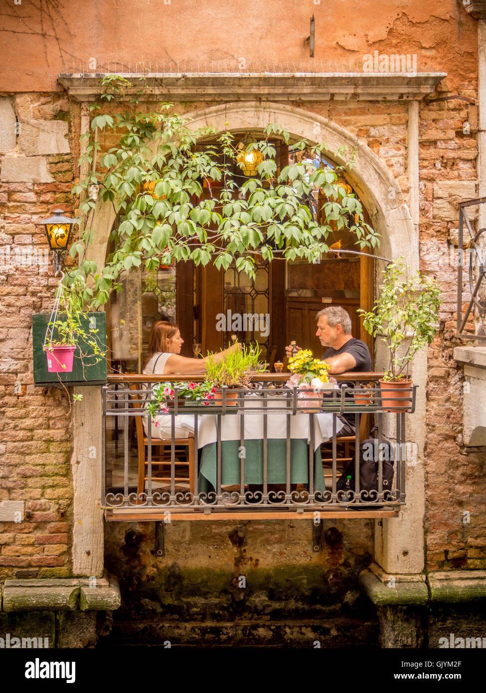 Mature couple dining on a balcony overlooking a canal in for Restaurants with balcony