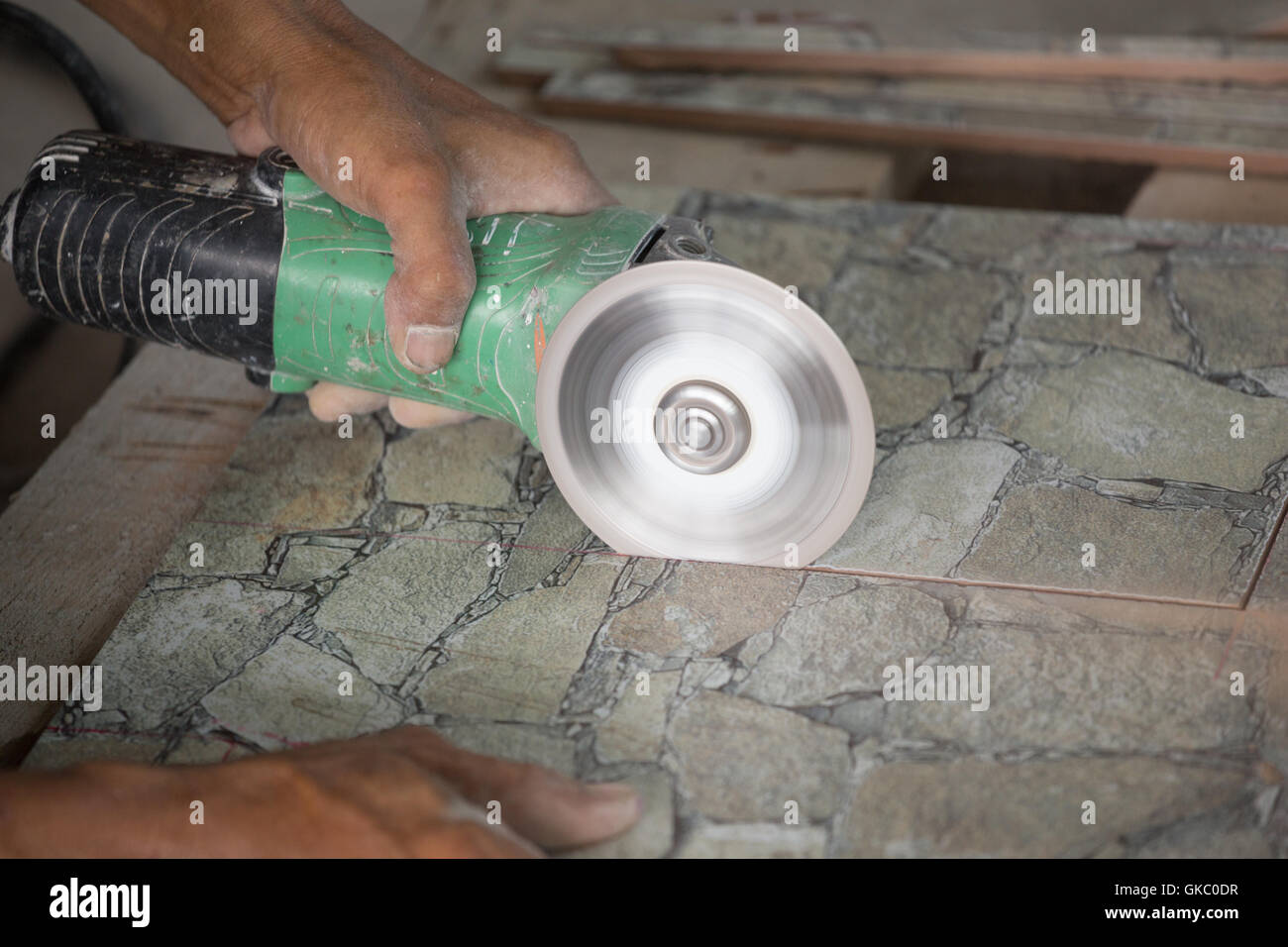 Worker cutting a tile using an angle grinder at construction site worker cutting a tile using an angle grinder at construction site dailygadgetfo Choice Image