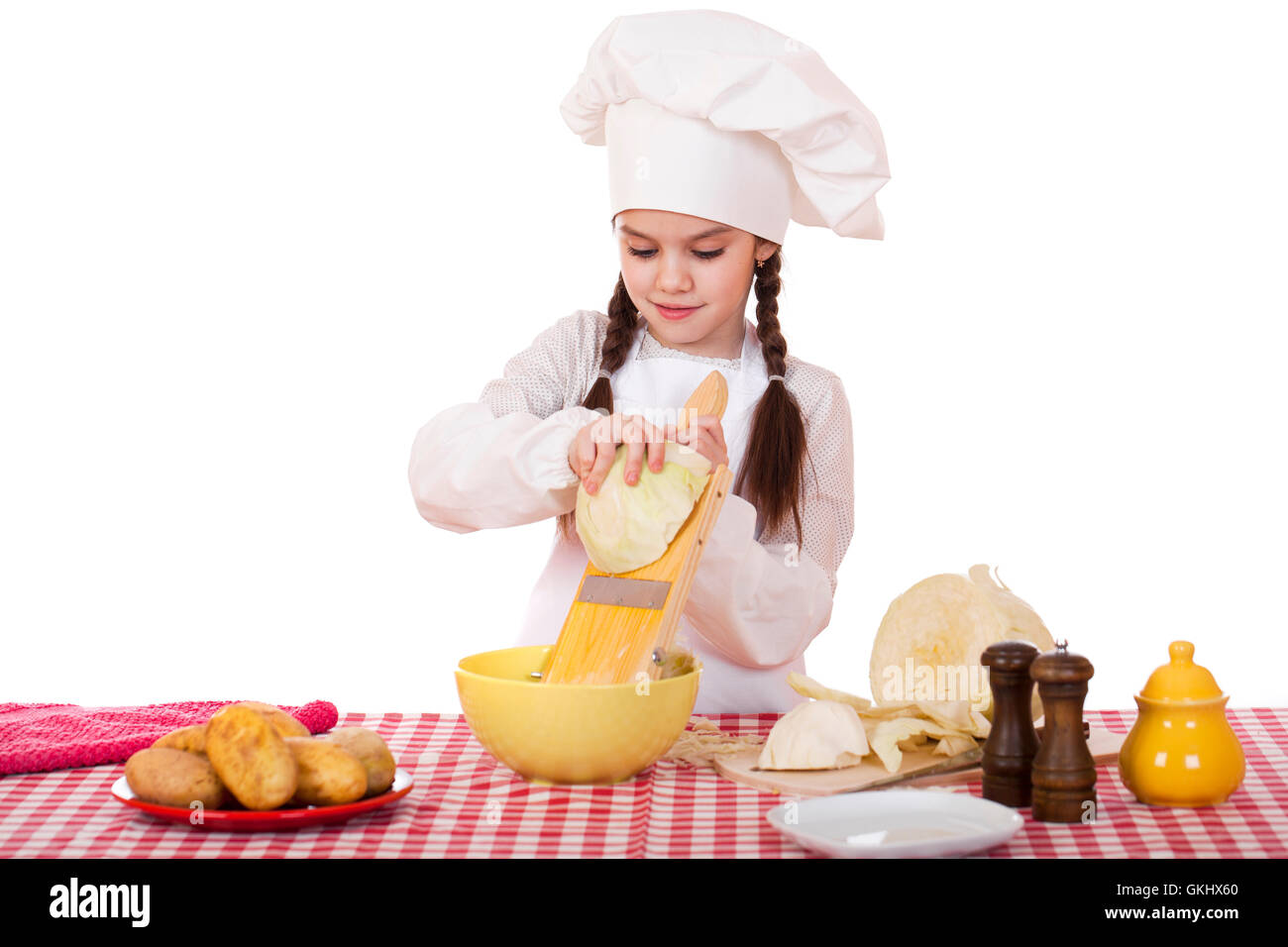 White apron and hat - Portrait Of A Little Girl In A White Apron And Chefs Hat Shred Cabbage In The Kitchen Isolated On White Background