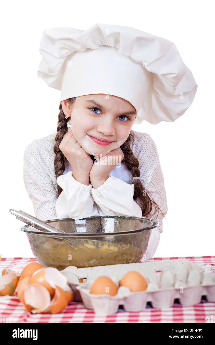 White apron girl - Portrait Of A Little Girl In A White Apron And Chefs Hat Knead The Dough In The Kitchen Isolated On A White Background