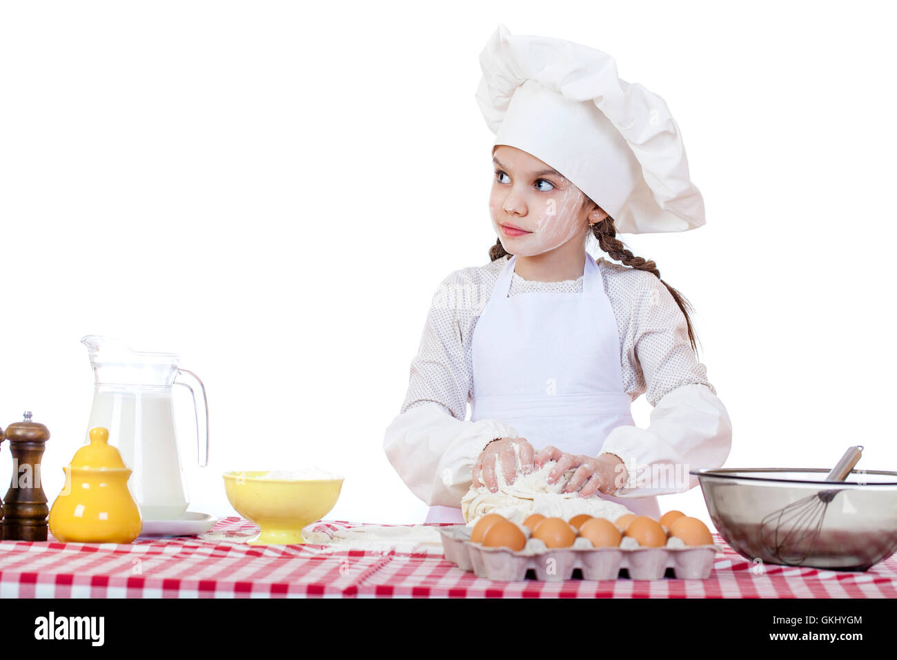 White apron and hat - Portrait Of A Little Girl In A White Apron And Chefs Hat Knead The Dough In The Kitchen Isolated On A White Background