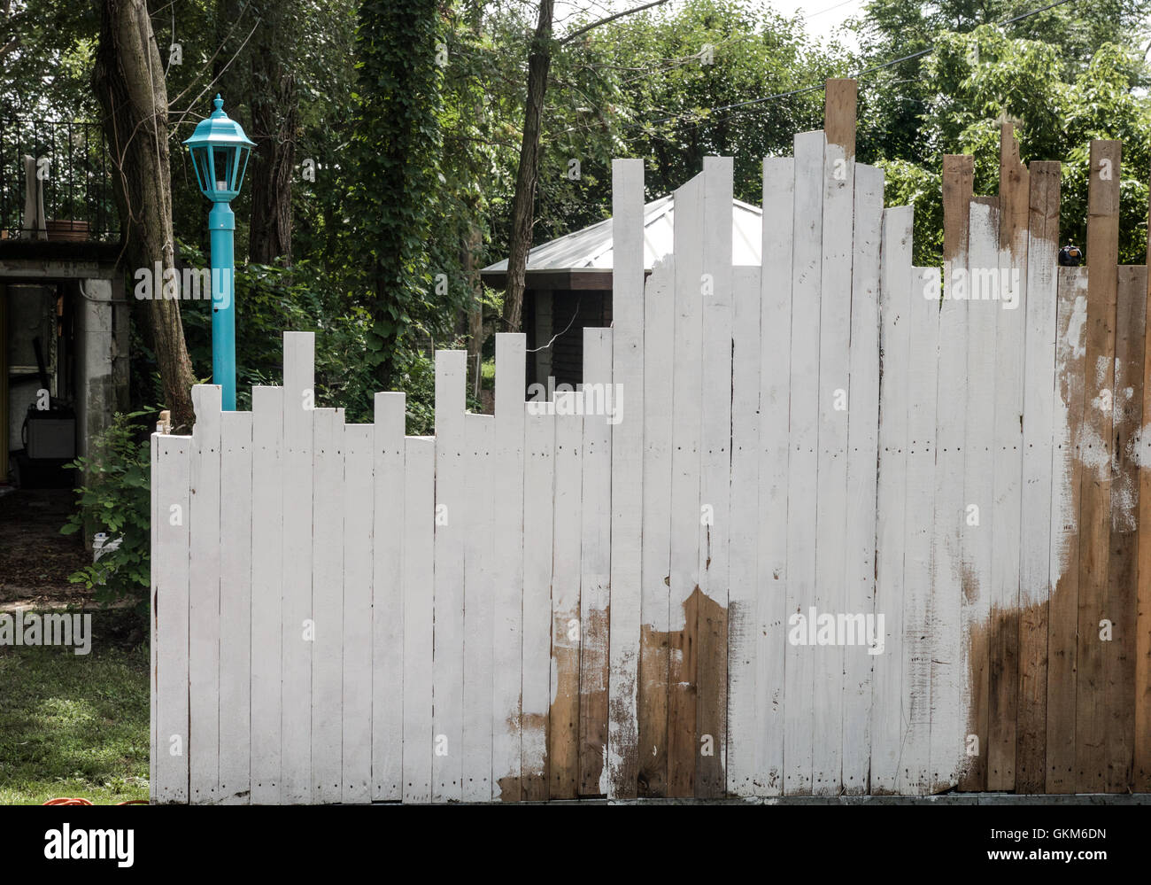 Wood outdoor lamp post - Uneven Boards In A Fence Are Partially Whitewashed With A Lamp Post And Garden In