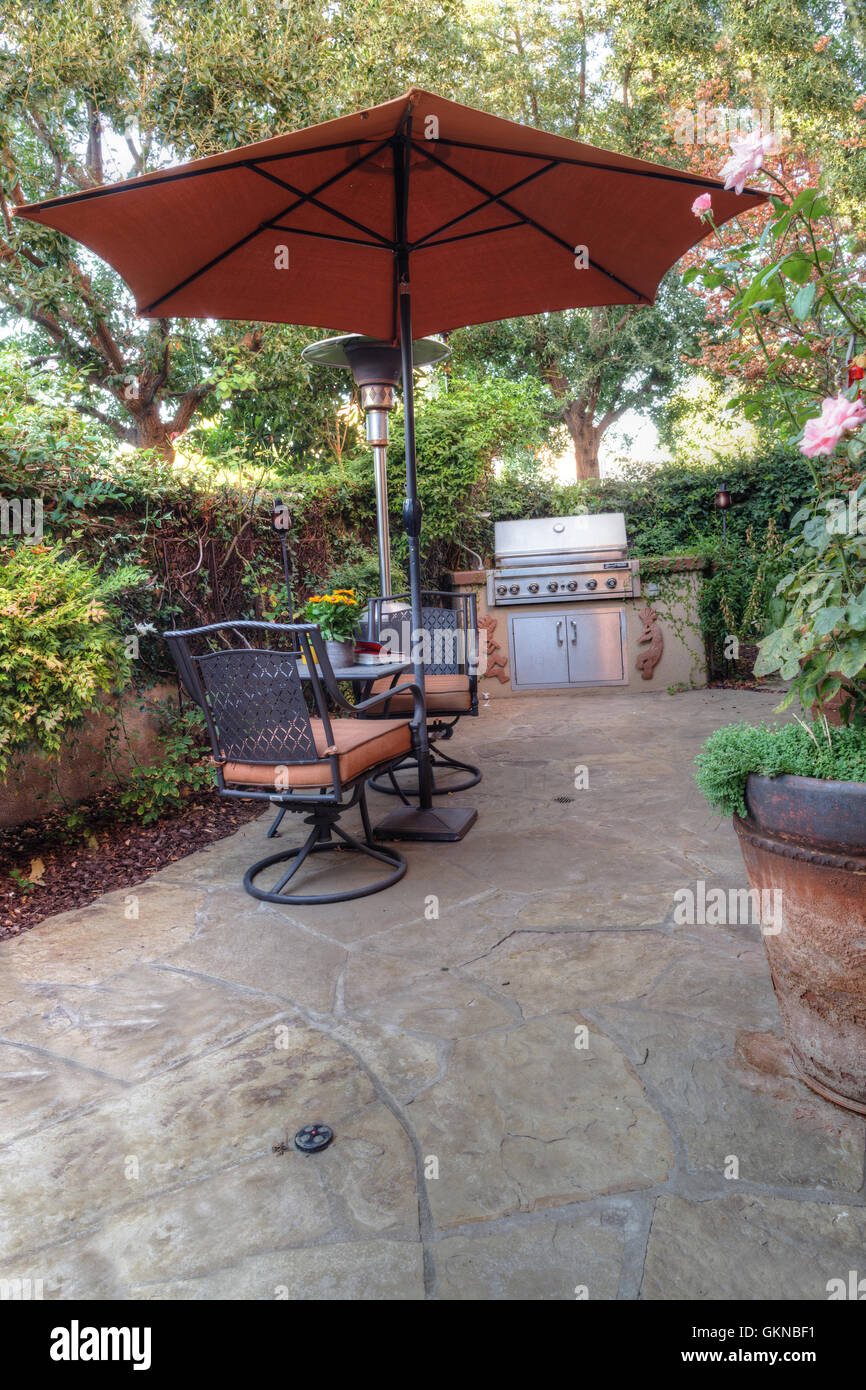 Irvine, CA, USA U2013 August 19, 2016: Chair, Table, Umbrella And Feng Shui  Garden Decor Located In A Private Small Patio With Plant