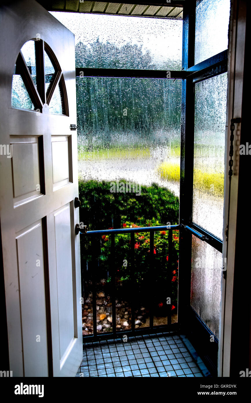 Looking out front door through screen showing rain Stock Photo ...