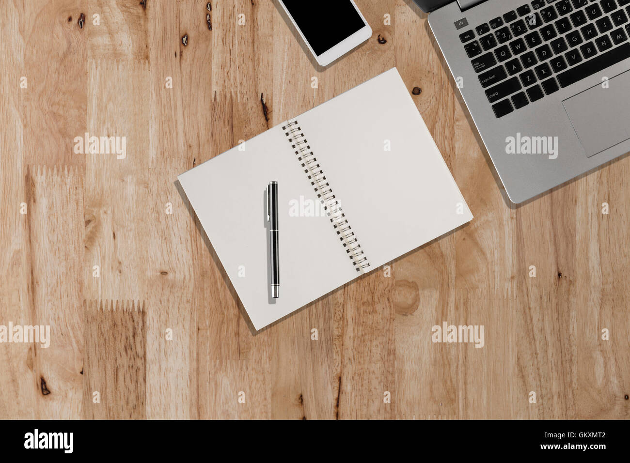laptop, smartphone, pen, notebook on wooden desk - top view with ...