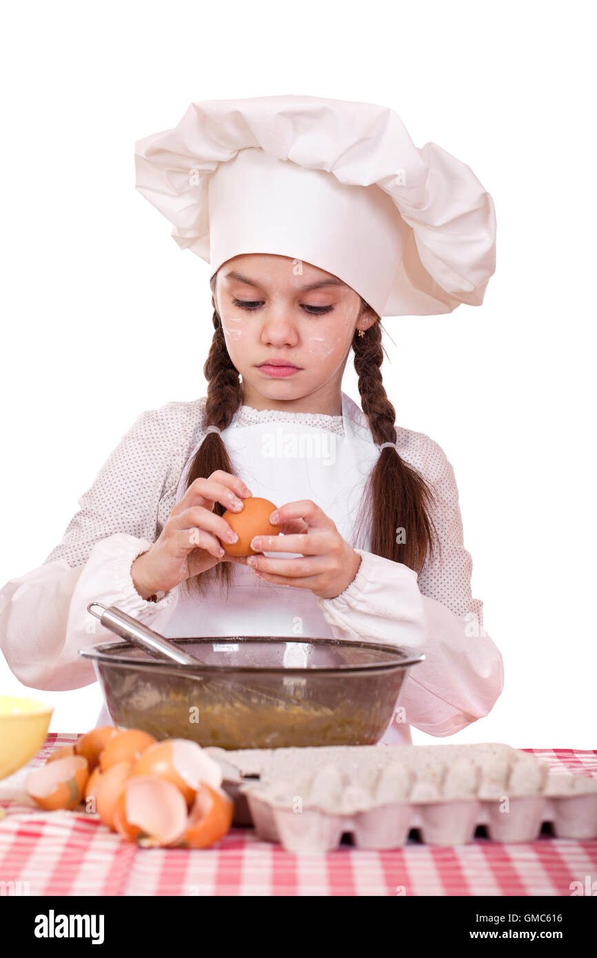 White apron girl - Little Cook Girl In A White Apron Breaks Eggs In A Deep Dish Isolated On White Background
