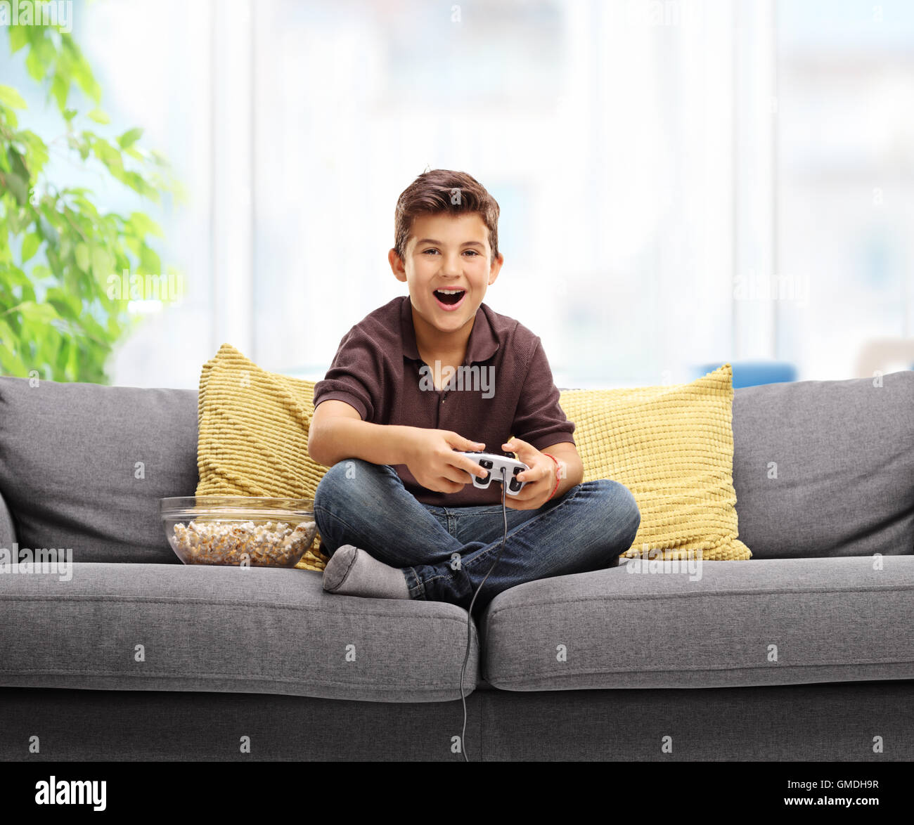 happy kid playing video games and sitting on a sofa stock. Black Bedroom Furniture Sets. Home Design Ideas