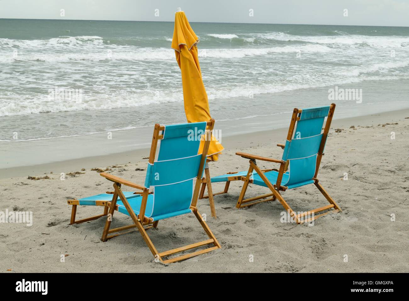 Pair Of Wooden Beach Chairs And Umbrella On Cocoa Beach, Florida