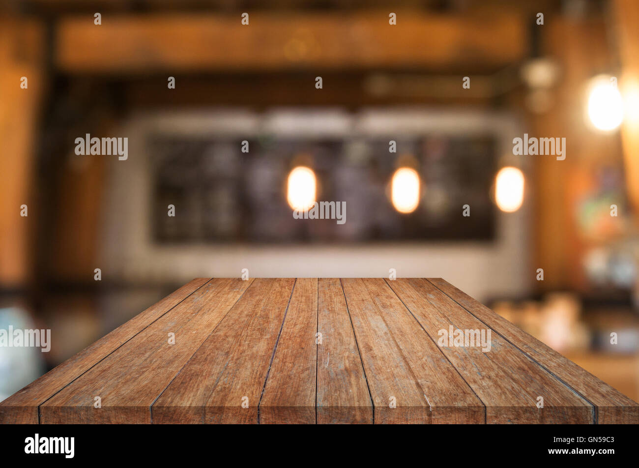 Perspective wooden table top with coffee shop blurred ...