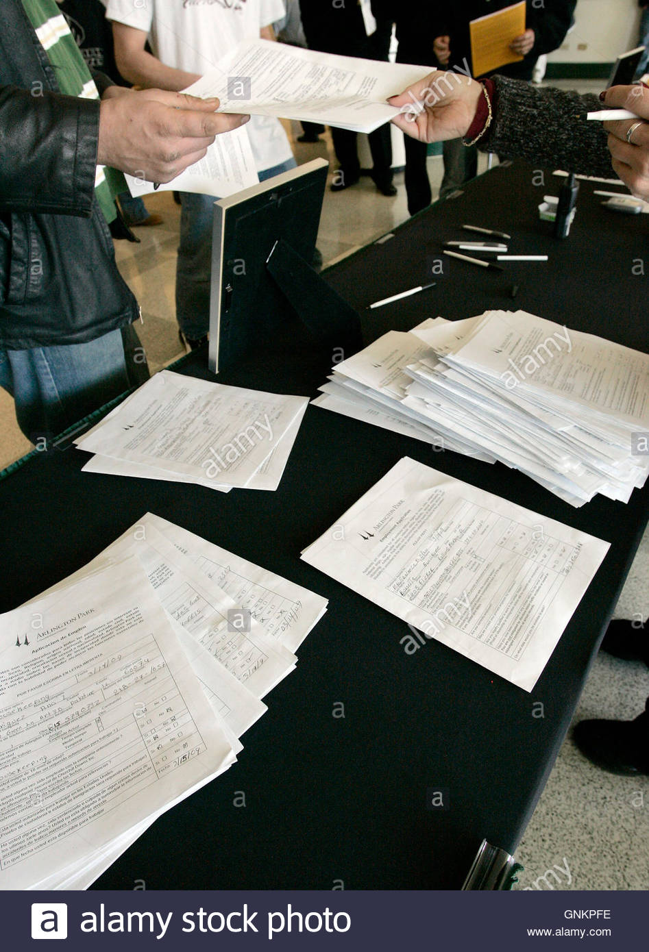 a job fair worker r receives an application from a man as a job fair worker r receives an application from a man as hundreds of people fill out applications for 300 400 temporary positions during a job fair at