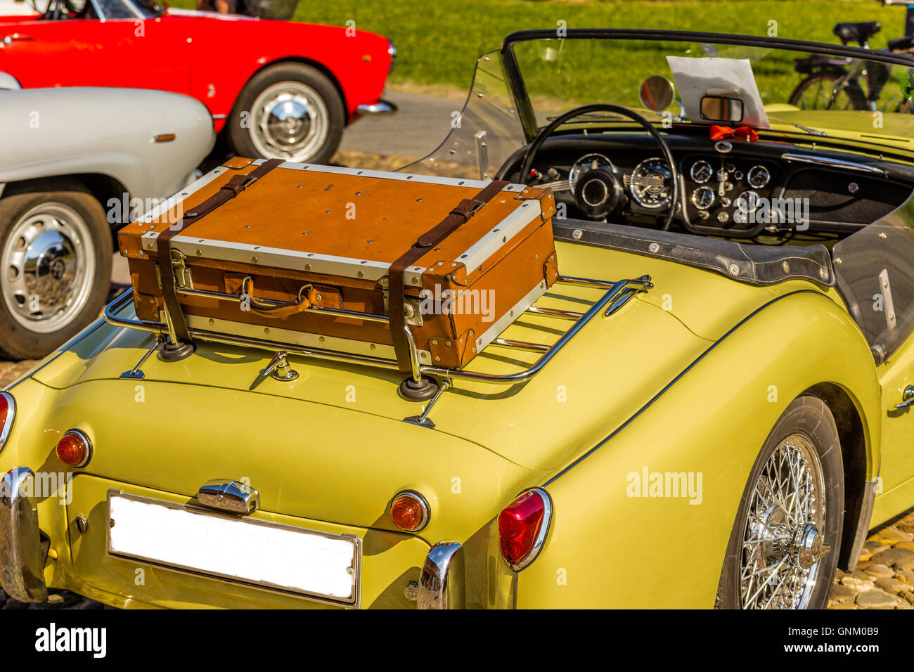old leather suitcase on the luggage rack of yellow vintage car ...