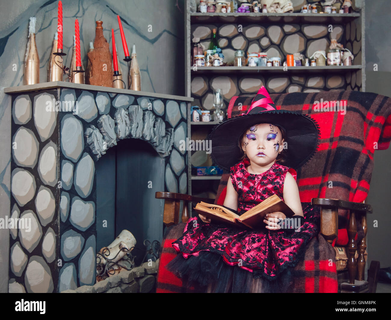 Girl in witch costume and make-up on her face sitting in a chair ...