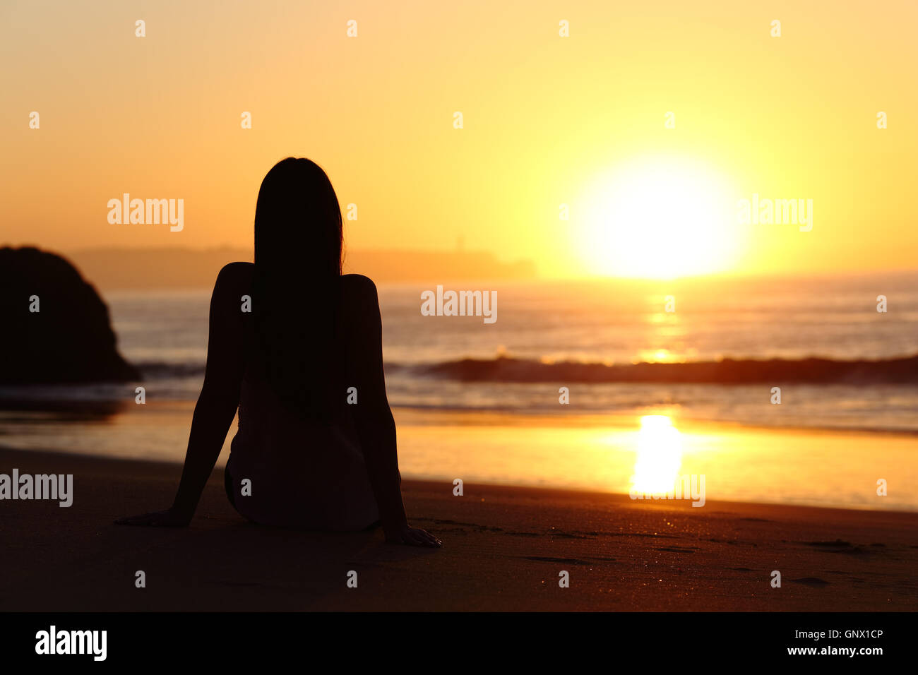 back view of a woman silhouette sitting on the sand of a beach watching sun at sunrise with the horizon and ocean