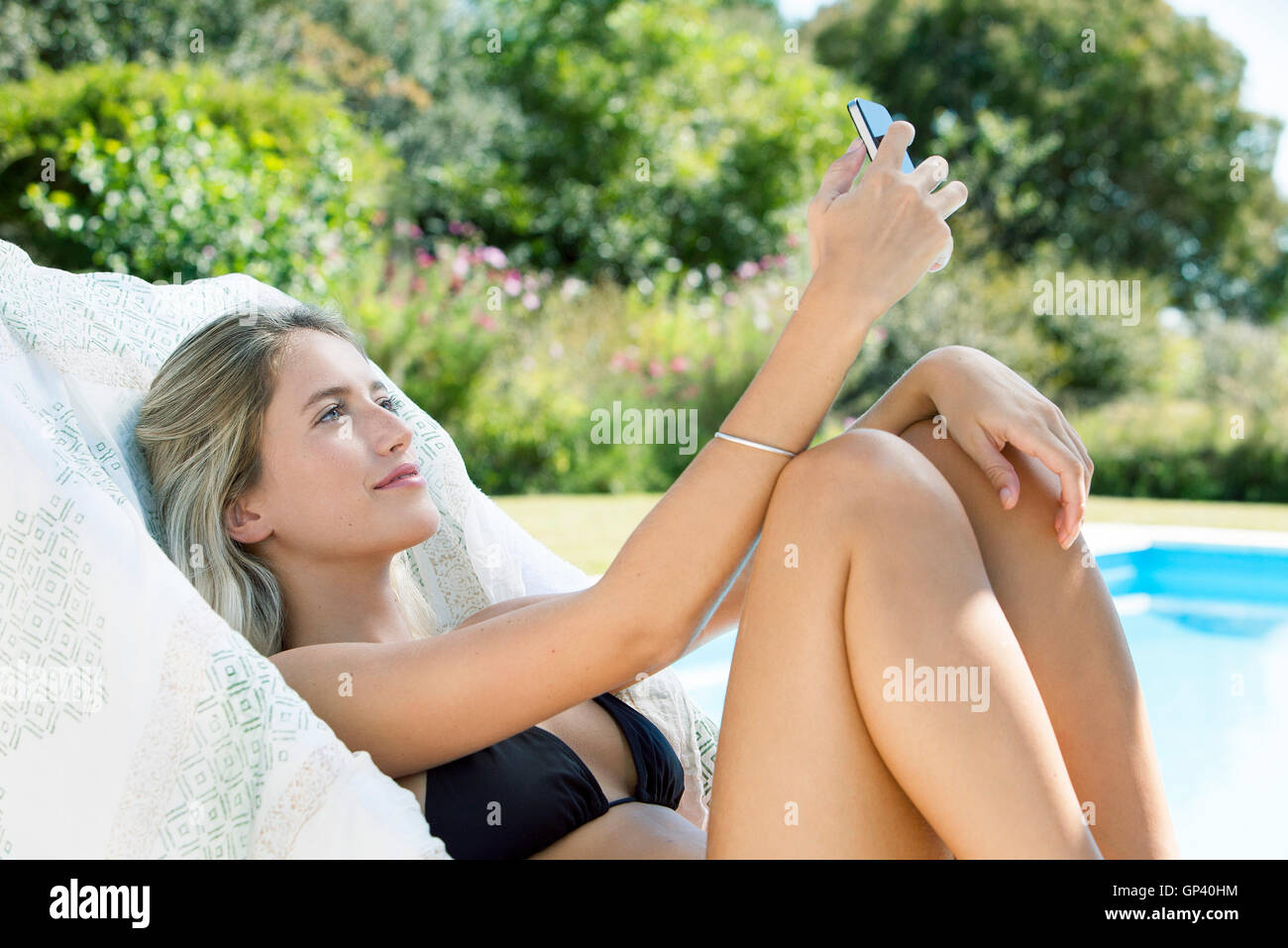 woman relaxing by pool using smartphone to take a selfie stock