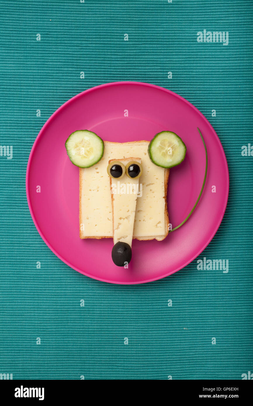 funny mouse made of bread and cheese on plate and green fabric