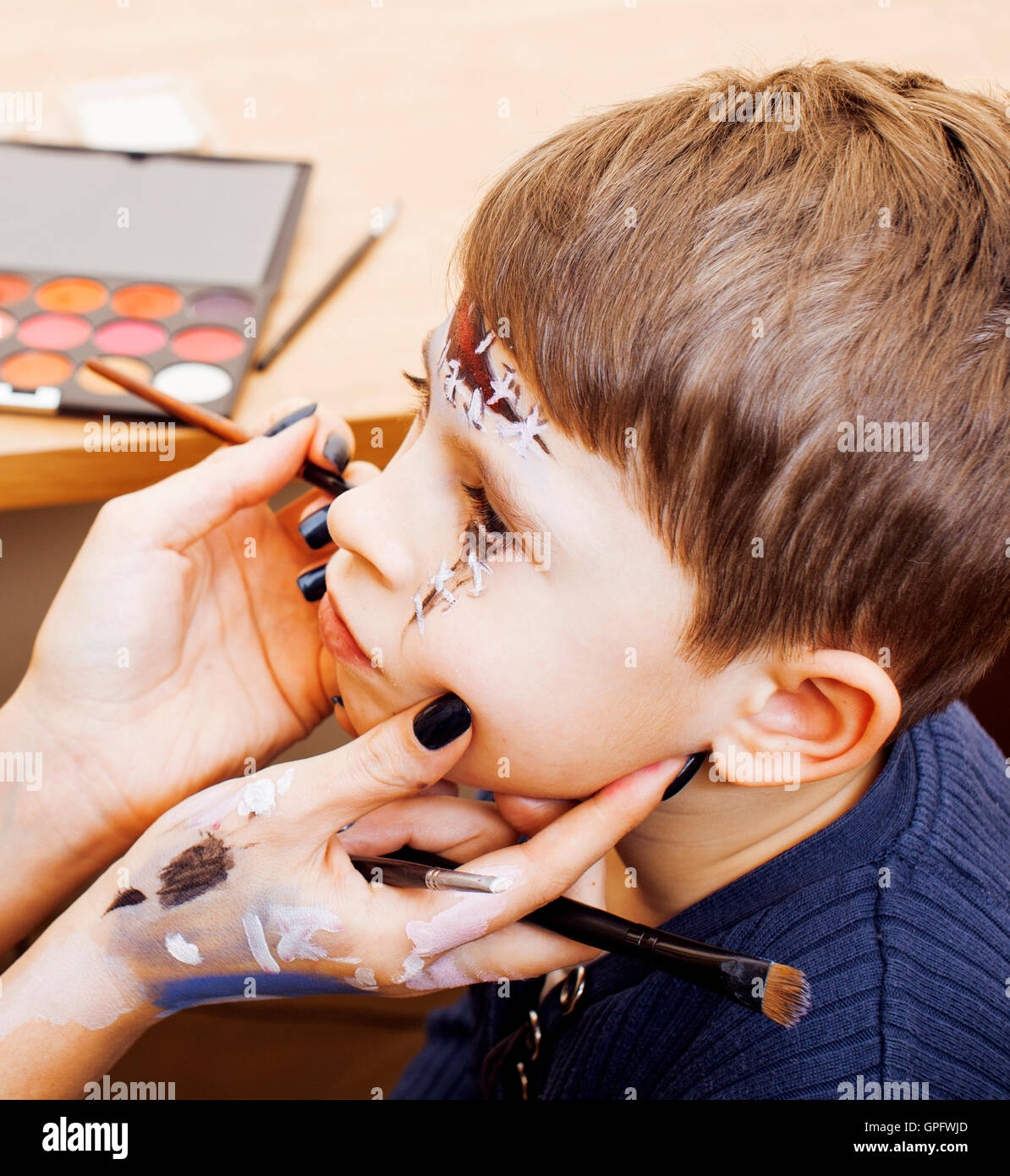 little cute child making facepaint on birthday party zombie Stock